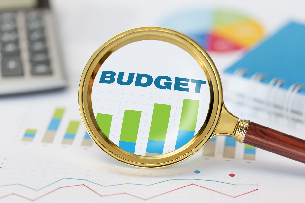 Magnifying glass and calculator on budget graph